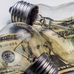 A lightbulb on dollar bill, energy saving concept